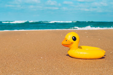 Inflatable Rubber Duck Swimming Ring On The Sand Near Sea On The Beach