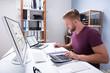 Leinwanddruck Bild Businessman Checking Invoice On Laptop