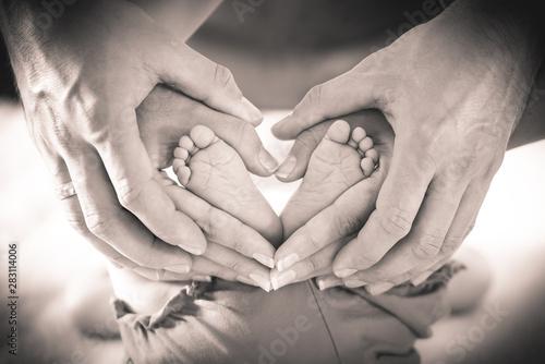 Foto auf Leinwand Texturen Eltern formen Herz um Babyfüße, sepia