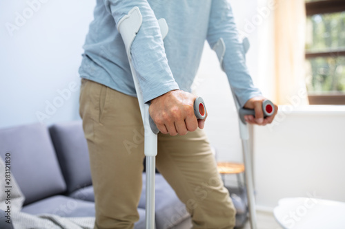 Papel de parede Disabled Man Using Crutches To Walk