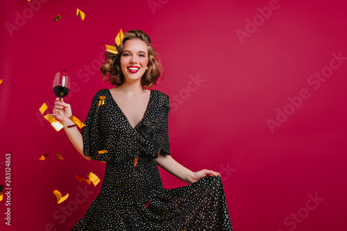 Blissful female model with shiny curly hair posing with wineglass on claret background. Emotional young woman wears black attire having fun at party with champagne and confetti and smiling. - 283124863