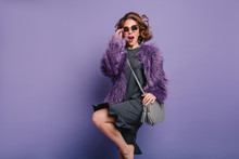 Studio Shot Of Curly Barefooted Girl In Fur Coat Jumping During Photoshoot. Charming Female Model In Purple Fluffy Jacket Dancing With Excited Face Expression.