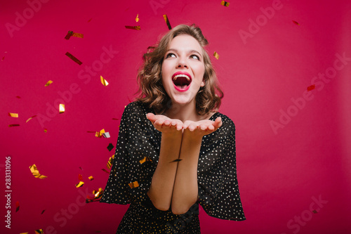 Lovable short-haired girl expressing positive emotions at party with confetti. Refined winsome lady in vintage black attire resting at festive. - 283131096