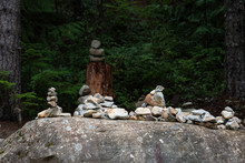 Collection Of Rock Cairns On Top Of A Large Boulder In The Forest