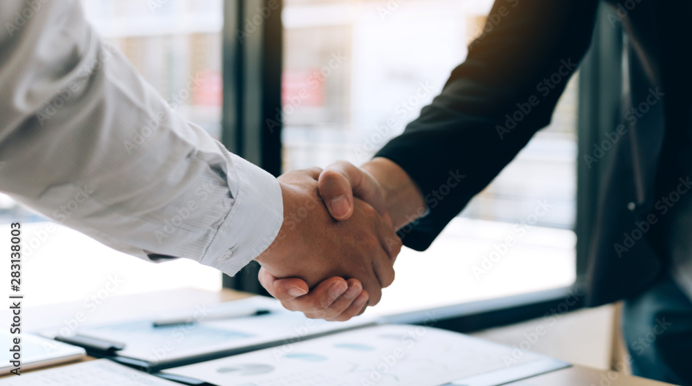 Fototapeta Entrepreneurs collaboration deal shaking hands in a modern office and financial paper graph on desk.