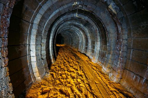 Fototapeta  Dark dirty abandoned uranium mine with rusty remnants of railway