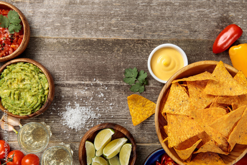 Fotografía  top view of Mexican nachos served with cheese sauce, guacamole and salsa on weat