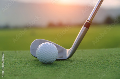 Poster Golf Golf ball and golf club in beautiful golf course at sunset background. Golf ball on green in golf course at Thailand