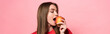 panoramic shot of young woman eating apple with closed eyes isolated on pink
