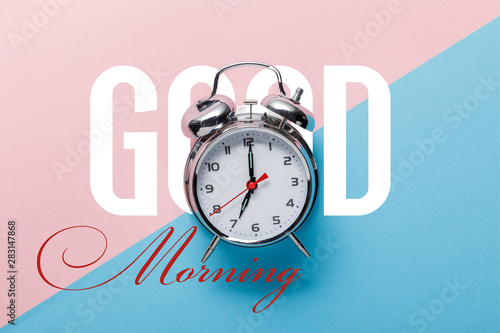 Fotografie, Tablou top view of classic silver alarm clock on pink and blue background with good mor