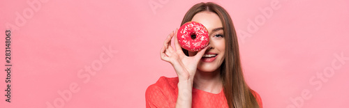 panoramic shot of attractive smiling girl holding sweet doughnut isolated on pin Canvas