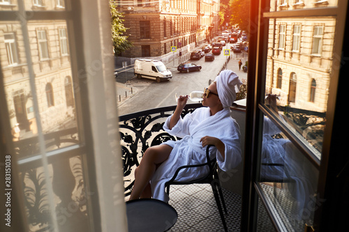Fotografie, Obraz  Beautiful blonde in a white coat enjoying a glass of white wine sitting on a hot