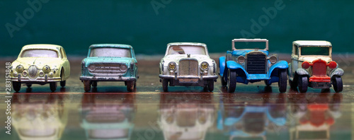 Fototapeta  a line of retro toy cars parked on a old wooden floor