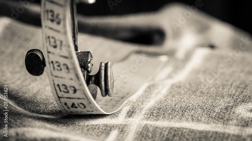 Fotografía  Closeup of vintage tailor machine with scissors, cloth and threads