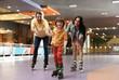 Leinwanddruck Bild - Happy family spending time at roller skating rink