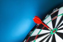 Red Arrow Hitting Target On Dart Board Against Blue Background. Space For Text