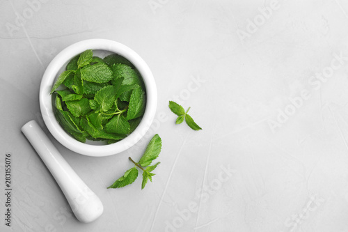 Obraz Fresh mint with mortar and pestle on grey background, flat lay. Space for text - fototapety do salonu