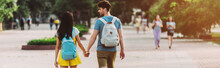 Panoramic Shot Of Man And Woman With Backpacks Walking And Holding Hands