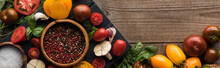 Panoramic Shot Of Black Tray With Pepper And Salt In Bowls, Chilli Pepper, Sliced Tomatoes And Garlic Near Scattered Vegetables On Wooden Table