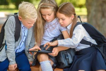 school friends, schoolchildren sitting on a bench in the park use a tablet, social media communication