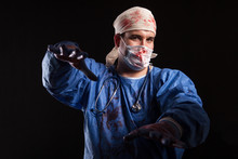Crazy Doctor With A Surgeon Mask And Scrubs Splattered With Blood For Halloween