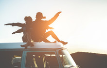 Happy Couple Silhouette Sitting On Top Of Minivan At Sunset - Young People Having Fun On Summer Vacation Traveling Around The World - Travel, Love, Van Lifestyle, Concept - Focus On Bodies