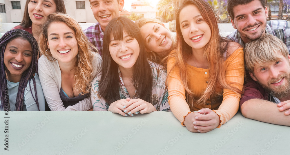 Fototapeta Happy millennial friends from diverse cultures and races having fun posing in front of smartphone camera - Youth and friendship concept - Young multiracial people smiling - Main focus on center faces