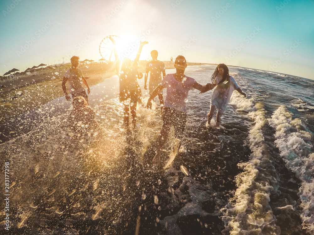 Fototapety, obrazy: Happy friends having fun on the beach at sunset - Young people playing inside sea water outdoor in summer vacation - Friendship, youth, travel concept - Soft focus on men faces