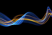 Long Exposure, Light Painting Photography.  Vibrant Streaks Of Neon Blue And Gold Color Against A Black Background.