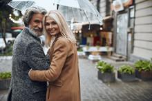 Smiling Couple Enjoying Rainy Day Stock Photo