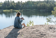 A Young Woman Sits On The Edge Of A Cliff Above A Quarry Filled With Water, Holding A Camera In Her Hands On A Summer Day And Takes Pictures Of The Landscape. Traveling As Lifestyle. Top-side View