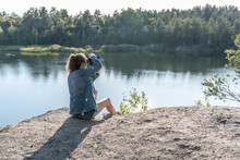 A Young Woman In Casual Jeans Clothes Sits On The Edge Of A Cliff Above A Quarry Filled With Water, Holding A Camera In Her Hands On A Summer Day And Takes Pictures Of The Landscape.