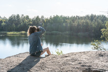 A Young Woman In Jeans Clothes Sits On The Edge Of A Cliff Above A Quarry Filled With Water, Holding A Camera In Her Hands On A Summer Day And Takes Pictures Of The Landscape. Traveling As Lifestyle