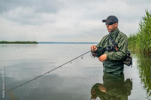 Fotobehang Vissen Fishing. Fisherman in action, man catch fish by spinning rod