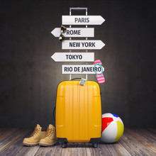 Yellow Suitcase And Signpost With Travel Destination.Tourism And  Travel Concept Background.