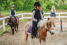 Children With Helmets And Protective Vests On Riding Pony Horses At Sunny Day On Ranch.