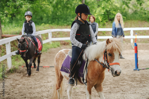 Fototapeta Children with helmets and protective vests on riding pony horses at sunny day on ranch