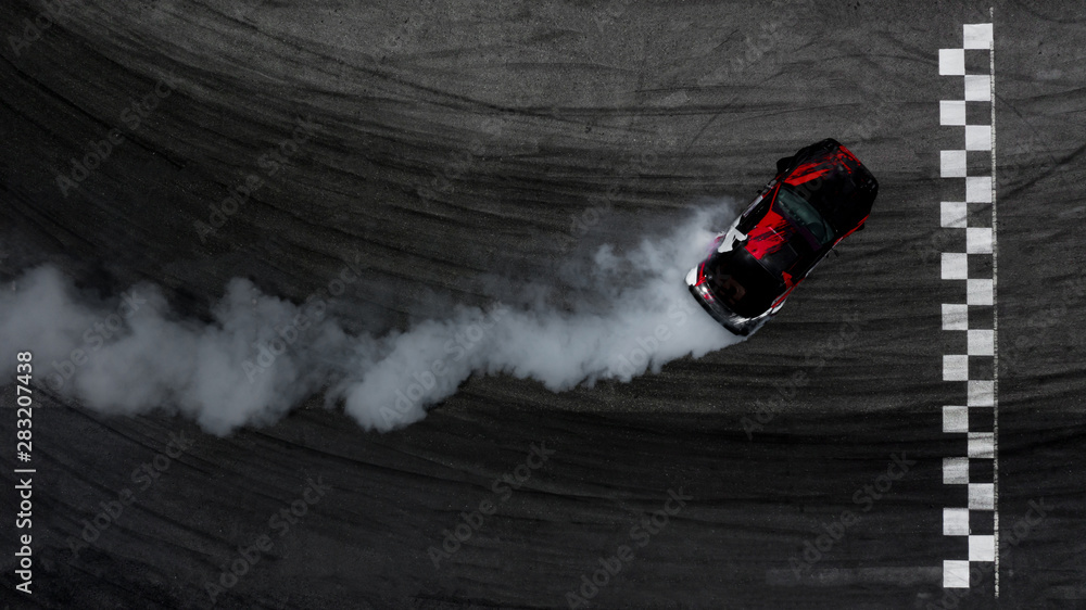 Aerial top view car drifting on asphalt race track with start and finish line and lots of smoke from burning tires, Auto or automobile background concept.