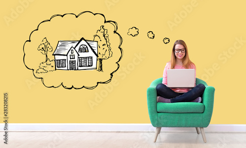 Fotografía  Dreaming of new home with young woman using her laptop in a chair