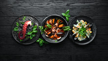 Set Of Seafood Dishes. Seafood On A Plate. On A Black Wooden Background. Top View. Free Copy Space.