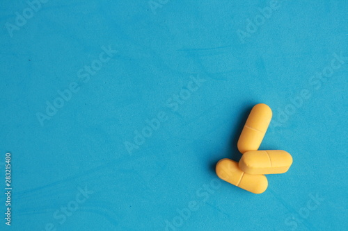 Stampa su Tela  orange elongated pharmacy pills on colored background