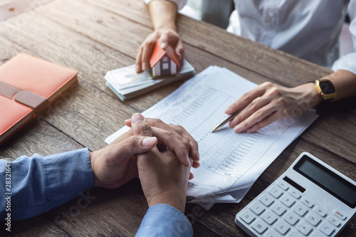 Fotomural Loan agreement, real estate agent or bank officer describes the loan interest to the customer, along with loan documents with a home-style pen and a replica money on a wooden table