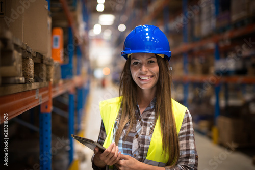 Cuadros en Lienzo Portrait of smiling woman in protective uniform with hardhat holding tablet in warehouse center