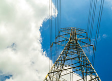 Electricity Pylons With Blue Sky And White Clouds. High Voltage Grid Tower With Wire Cable At Distribution Station. High Voltage Electric Tower And Transmission Lines.