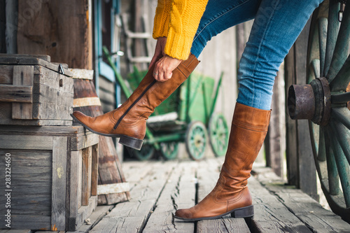 Fototapeta Woman fasten zipper on her leather boot obraz