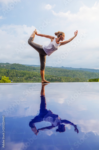 Stampa su Tela  Caucasian woman practicing yoga by the pool