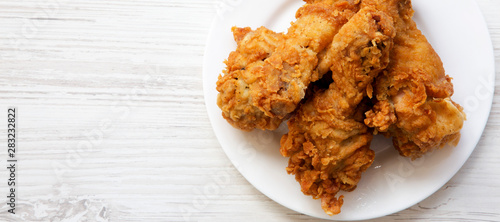 Fried chicken drumsticks on a white round plate, top view Wallpaper Mural