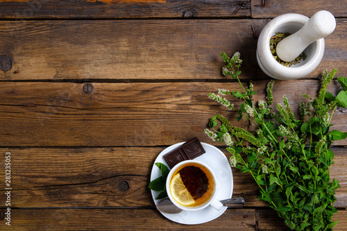 Foto auf Leinwand Schokolade White cup of mint tea with lemon and chocolate on a brown wooden background, top view, empty space