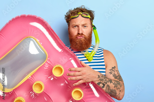Fotografia Displeased bearded guy poses with pink air mattress, wears swimming goggles and