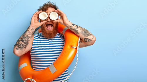 Fotografía  Funny redhead holiday maker wears sailor vest, poses with inflated lifebuoy, rea